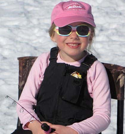 child smiling holding a fishing rod ice fishing